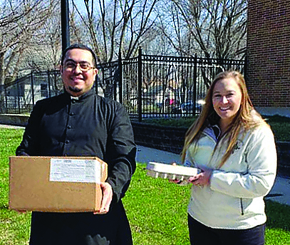 Father Luis Mejia and Kandice Roethler offer food to ne